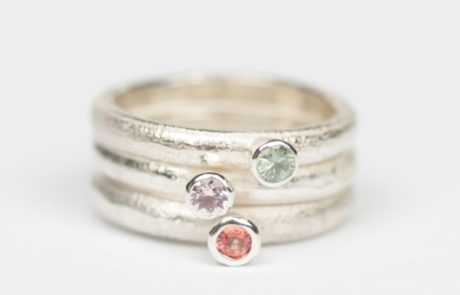 A stack of three sliver rings each with a single coloured stone in green, purple and red.