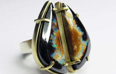 Chunky silver ring with a stone in two halves. The stone is black, terracotta and green.