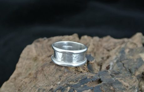 A wide silver ring, simple design.