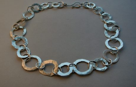 A silver necklace with hammered rings