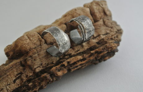 Two silver earrings resting on wood