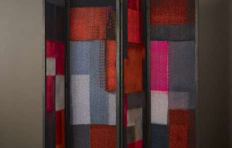 Geometric textile screen with four panels. Red, grey, white and pink